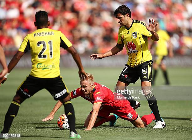 James Jeggo of Adelaide United is brought down by Vince Lia of Wellington Phoenix during the round 12 ALeague match between Adelaide United and the...