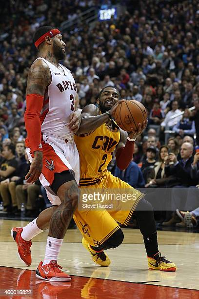 TORONTO ON DECEMBER 5 James Johnson defends as Kyrie Irving goes to the basket as the Toronto Raptors lose to the Cleveland Cavaliers 10591 at the in...