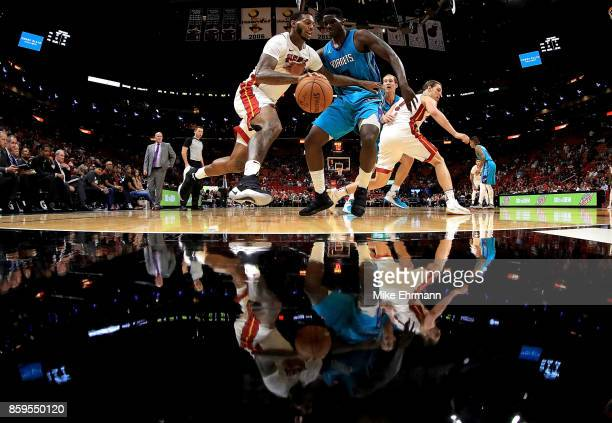 James Johnson of the Miami Heat drives on Johnny O'Bryant III of the Charlotte Hornets during a preseason game at American Airlines Arena on October...