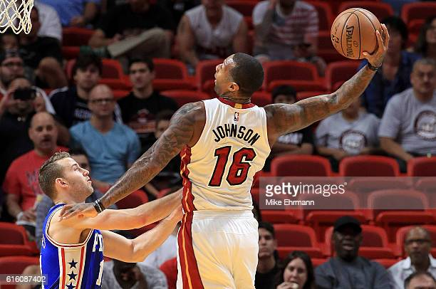 James Johnson of the Miami Heat dunks over Nik Stauskas of the Philadelphia 76ers during a preseason game at American Airlines Arena on October 21...