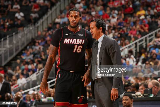 James Johnson of the Miami Heat speaks with Head coach Erik Spoelstra of the Miami Heat during the preseason game against the Philadelphia 76ers on...