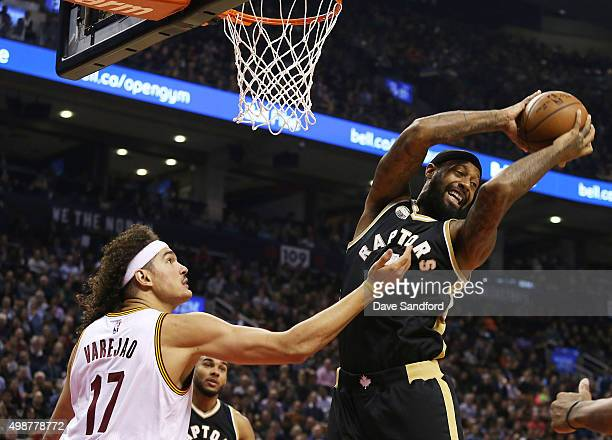 James Johnson of the Toronto Raptors grabs a rebound over Anderson Varejao of the Cleveland Cavaliers on November 25 2015 at Air Canada Centre in...