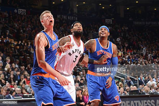 James Johnson of the Toronto Raptors looks for the rebound against Kristaps Porzingis and Carmelo Anthony of the New York Knicks during the game on...