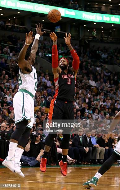 James Johnson of the Toronto Raptors shoots against Jae Crowder of the Boston Celtics in the first half at TD Garden on April 14 2015 in Boston...