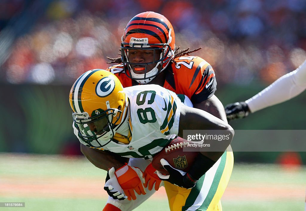 James Jones #89 of the Green Bay Packers is tackled by Adam Jones #24 of the Cincinnati Bengals during the game at Paul Brown Stadium on September 22, 2013 in Cincinnati, Ohio.