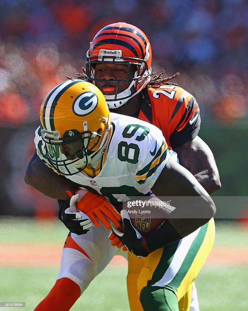 James Jones #89 of the Green Bay Packers is tackled by Adam Jones #24 of the Cincinnati Bengals during the game at Paul Brown Stadium on September 22, 2013 in Cincinnati, Ohio.