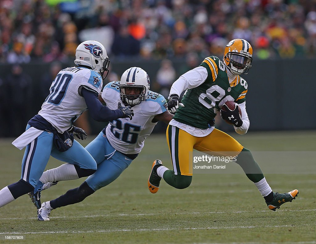 James Jones #89 of the Green Bay Packers runs against Jason McCourty #30 and Jordan Babineaux # 26 of the Tennessee Titans at Lambeau Field on December 23, 2012 in Green Bay, Wisconsin. The Packers defeated the Titans 55-7.
