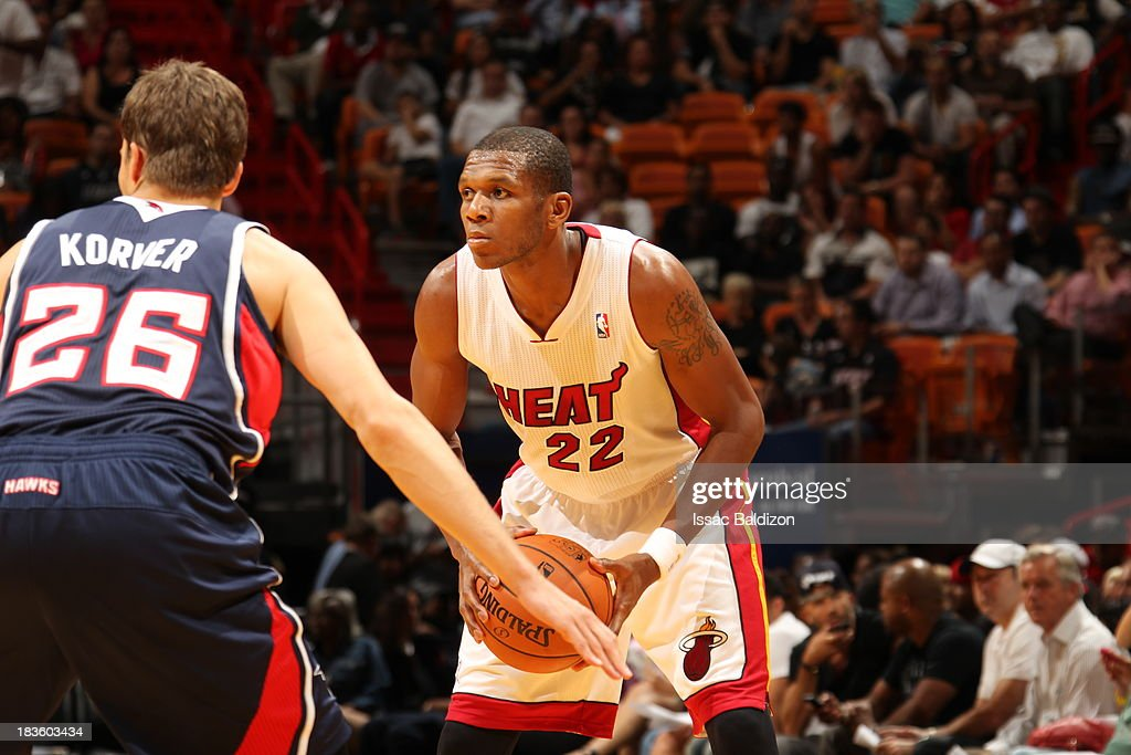 James Jones #22 of the Miami Heat looks for the open man against <a gi-track='captionPersonalityLinkClicked' href=/galleries/search?phrase=Kyle+Korver&family=editorial&specificpeople=202504 ng-click='$event.stopPropagation()'>Kyle Korver</a> #26 of the Atlanta Hawks during a game on October 7, 2013 at American Airlines Arena in Miami, Florida.