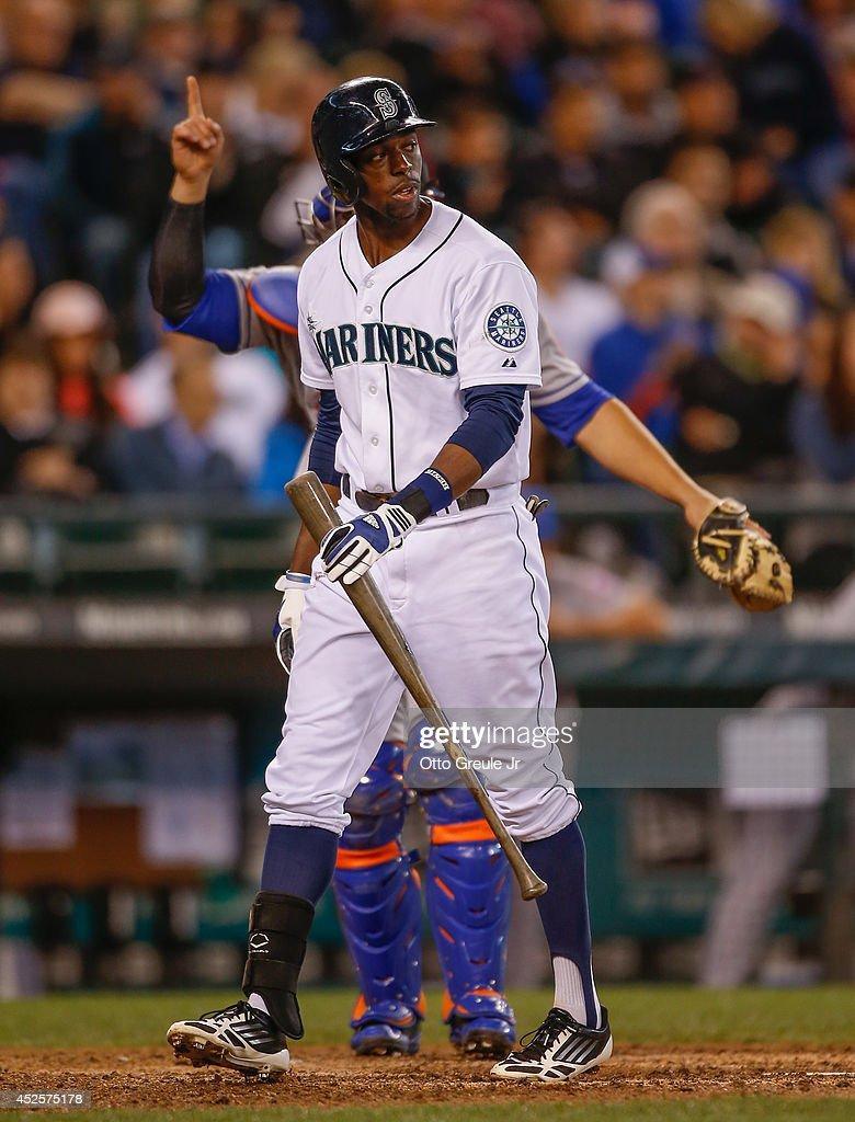 James Jones of the Seattle Mariners heads back to the dugout after striking out as catcher Anthony Recker of the New York Mets signals one out in the...