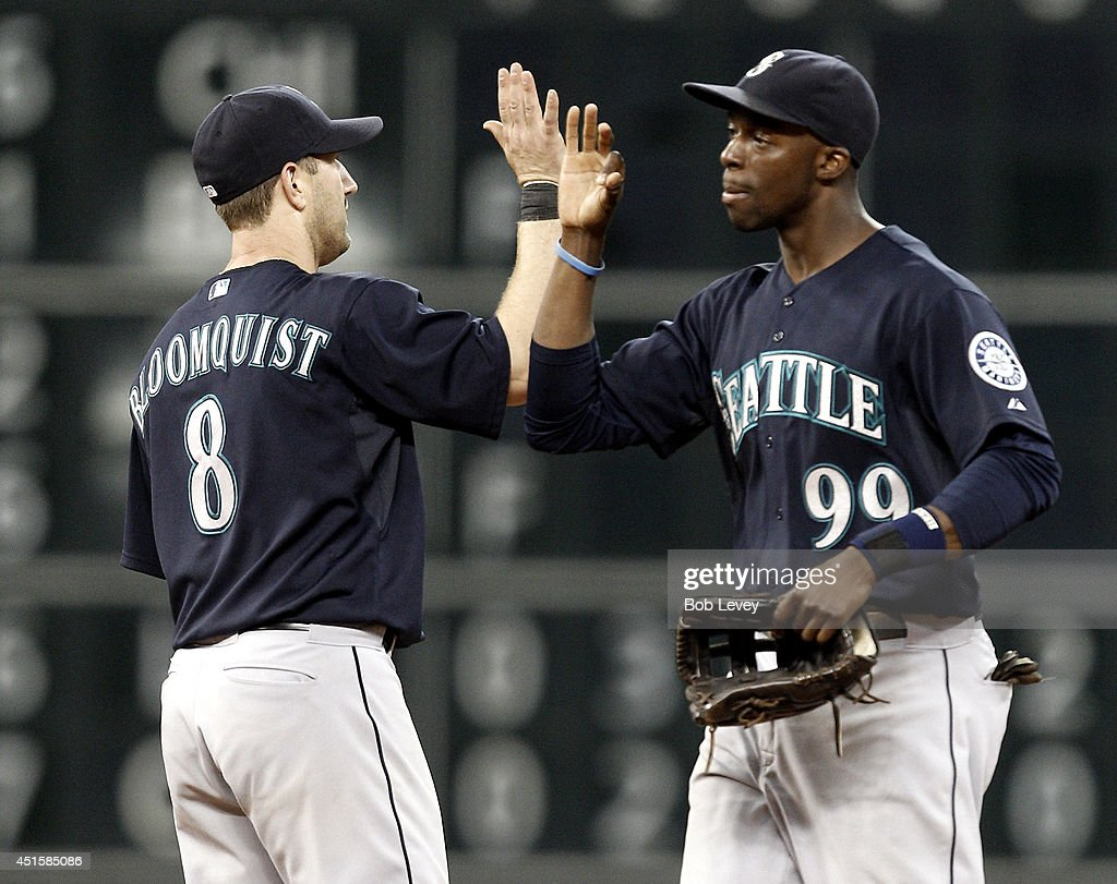 James Jones #99 of the Seattle Mariners high fives Willie Bloomquist #8 after the final out after the game against the Houston Astros at Minute Maid Park on July 1, 2014 in Houston, Texas.
