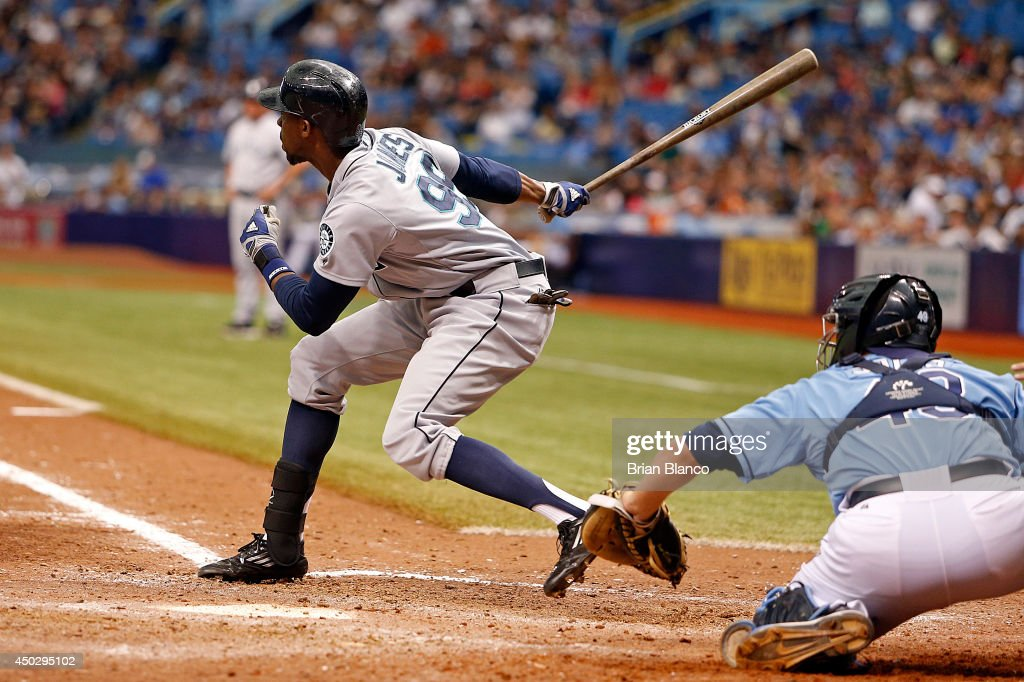 James Jones of the Seattle Mariners hits a tworun triple in front of catcher Ali Solis of the Tampa Bay Rays during the ninth inning of a game on...