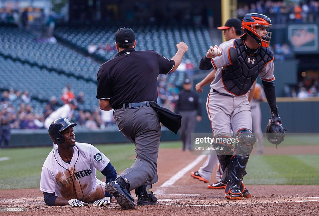 James Jones of the Seattle Mariners is called out at the plate by home plate umpire Jim Reynolds while attempting to score against catcher Caleb...