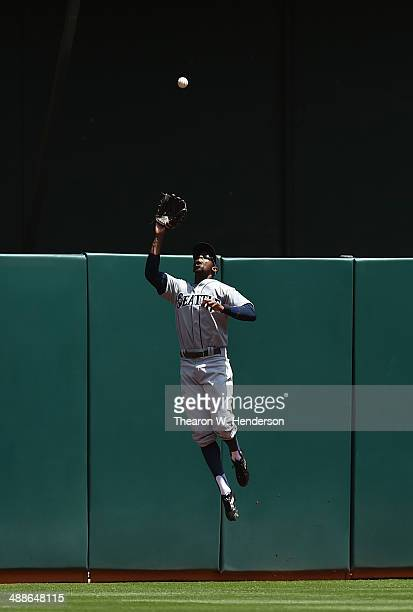James Jones of the Seattle Mariners leaps at the wall to take a hit away from Josh Donaldson of the Oakland Athletics in the bottom of the first...