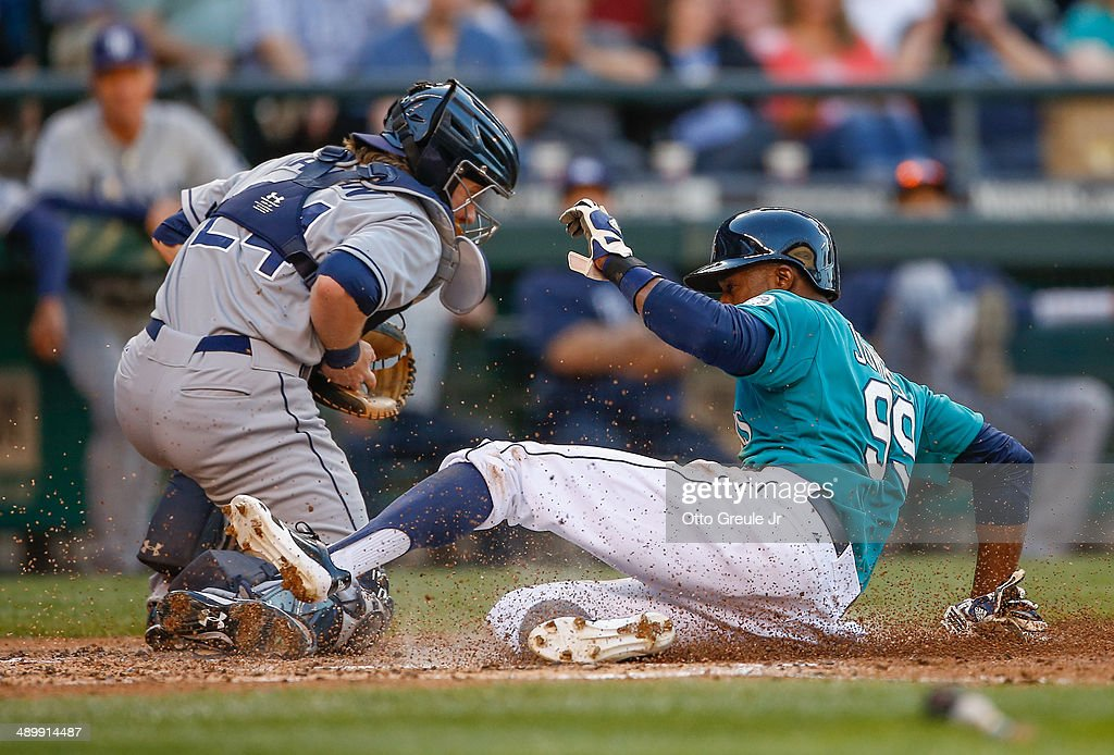 James Jones of the Seattle Mariners scores against catcher Ryan Hanigan of the Tampa Bay Rays on a sacrifice fly by Robinson Cano in the second...