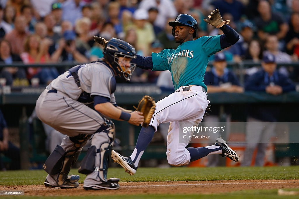 James Jones of the Seattle Mariners scores against catcher Ryan Hanigan of the Tampa Bay Rays at Safeco Field on May 12 2014 in Seattle Washington