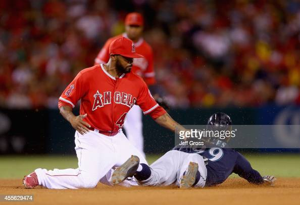 James Jones of the Seattle Mariners slides under the tag of second baseman Howie Kendrick of the Los Angeles Angels of Anaheim and steals second base...