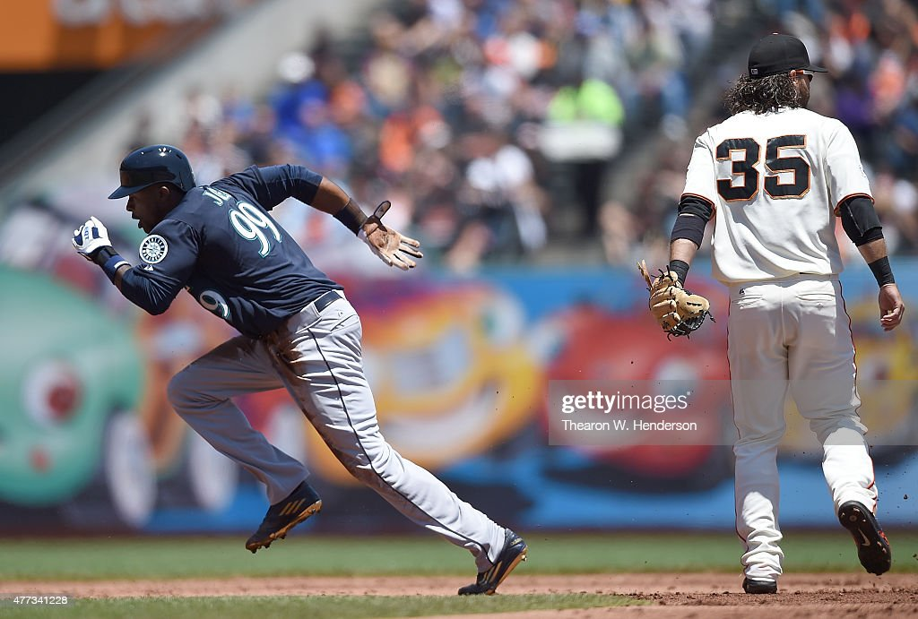 James Jones of the Seattle Mariners steals second base and races for third on a throwing error by catcher Andrew Susac of the San Francisco Giants in...