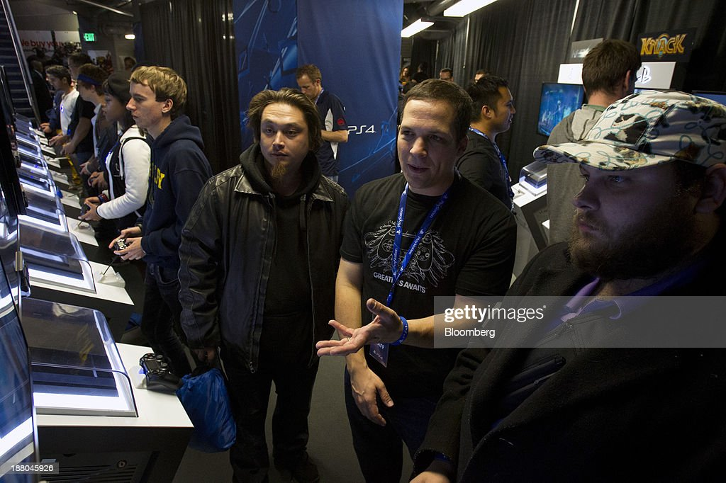 James Joy, employee at Sony Corp., center right, speaks with gamers Eli Adriano, center left, and Justin Hubbard, right, about the video game Tiny Brains during the Sony PlayStation 4 midnight launch event in San Francisco, California, U.S., on Thursday, Nov. 14, 2013. Sony Corp., poised to release the PlayStation 4 game console this week, is confident it can meet analysts' sales estimates of 3 million units by year-end, exploiting an early advantage over Microsoft Corp.'s Xbox One. Photographer: Erin Lubin/Bloomberg via Getty Images