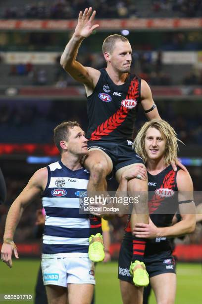 James Kelly of the Bombers celebrates the win on top of former teammate Joel Selwood of the Cats and teammate Dyson Heppell in his 300th match during...