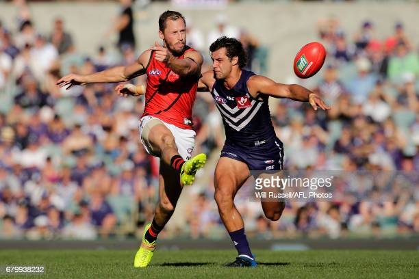 James Kelly of the Bombers kicks the ball under pressure from Brady Grey of the Dockers during the round seven AFL match between the Fremantle...