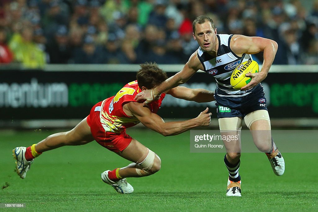 James Kelly of the Cats fends off a tackle by David Swallow of the Suns during the round ten AFL match between the Geelong Cats and the Gold Coast Suns at Simonds Stadium on June 1, 2013 in Geelong, Australia.