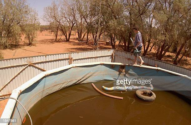 James Lacey starts to clean the family swimming pool after a severe dust storm polluted the water at Pineview Station on October 25 2002 in Broken...