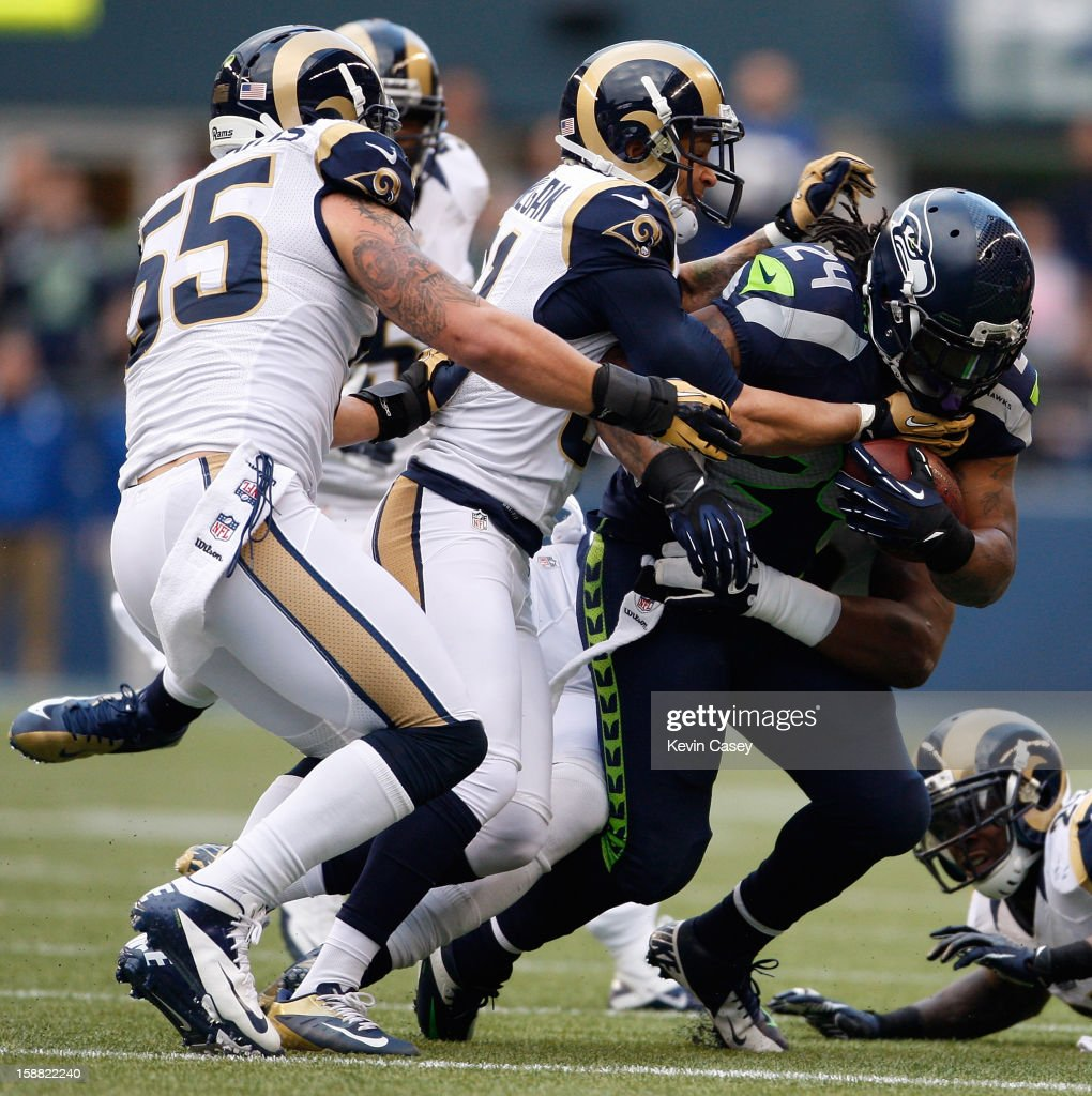 James Laurinaitis #55 and Cortland Finnegan #31 of the St. Louis Rams both tackle Marshawn Lynch (R) #24 of Seattle Seahawks at CenturyLink Field on December 30, 2012 in Seattle, Washington.