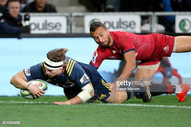 James Lentjes of the Highlanders dives over to score a try while in the tackle of Quade Cooper of the Reds during the round 17 Super Rugby match...