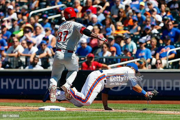 James Loney of the New York Mets holds onto a wide throw for a firstinning force out against Odubel Herrera of the Philadelphia Phillies at Citi...