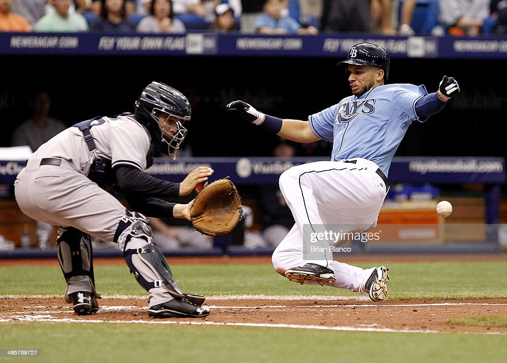 James Loney #21 of the Tampa Bay Rays beats catcher John Ryan Murphy #66 of the New York Yankees to home plate as he scores off of teammate Matt Joyce's sacrifice fly during the seventh inning of a game on April 20, 2014 at Tropicana Field in St. Petersburg, Florida.
