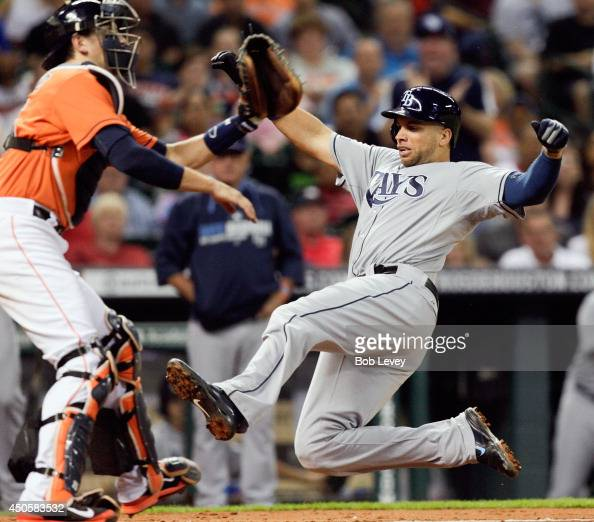 James Loney of the Tampa Bay Rays slides safely at home in the fifth inning as Jason Castro of the Houston Astros awaits the throw at Minute Maid...