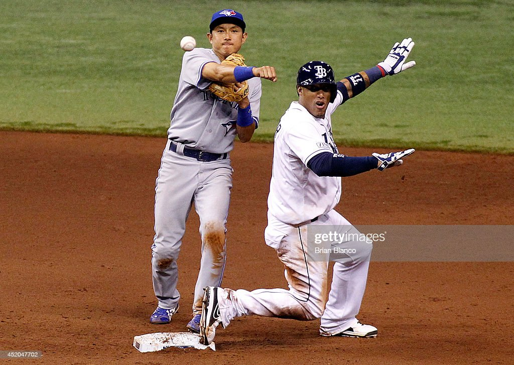 <a gi-track='captionPersonalityLinkClicked' href=/galleries/search?phrase=James+Loney&family=editorial&specificpeople=636293 ng-click='$event.stopPropagation()'>James Loney</a> #21 of the Tampa Bay Rays slides safely into second base as second baseman <a gi-track='captionPersonalityLinkClicked' href=/galleries/search?phrase=Munenori+Kawasaki&family=editorial&specificpeople=690355 ng-click='$event.stopPropagation()'>Munenori Kawasaki</a> #66 of the Toronto Blue Jays makes the throw to first base for the out on Logan Forsythe during the sixth inning of a game on July 11, 2014 at Tropicana Field in St. Petersburg, Florida.