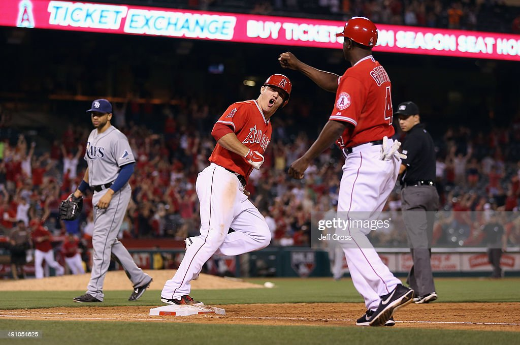 James Loney #21 of the Tampa Bay Rays walks off the field, as Mike Trout #27 of the Los Angeles Angels of Anaheim celebrates his three-run walk off home run with first base coach Alfredo Griffin #4 at Angel Stadium of Anaheim on May 15, 2014 in Anaheim, California. The Angels defeated the Rays 6-5.