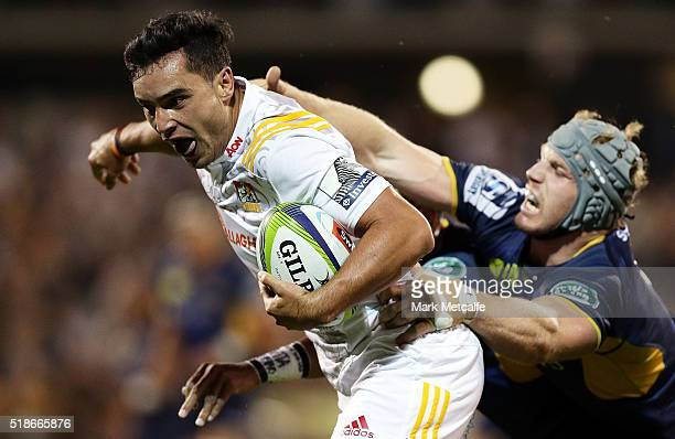 James Lowe of the Chiefs evades the tackle of David Pocock of the Brumbies to score a try during the round six Super Rugby match between the Brumbies...