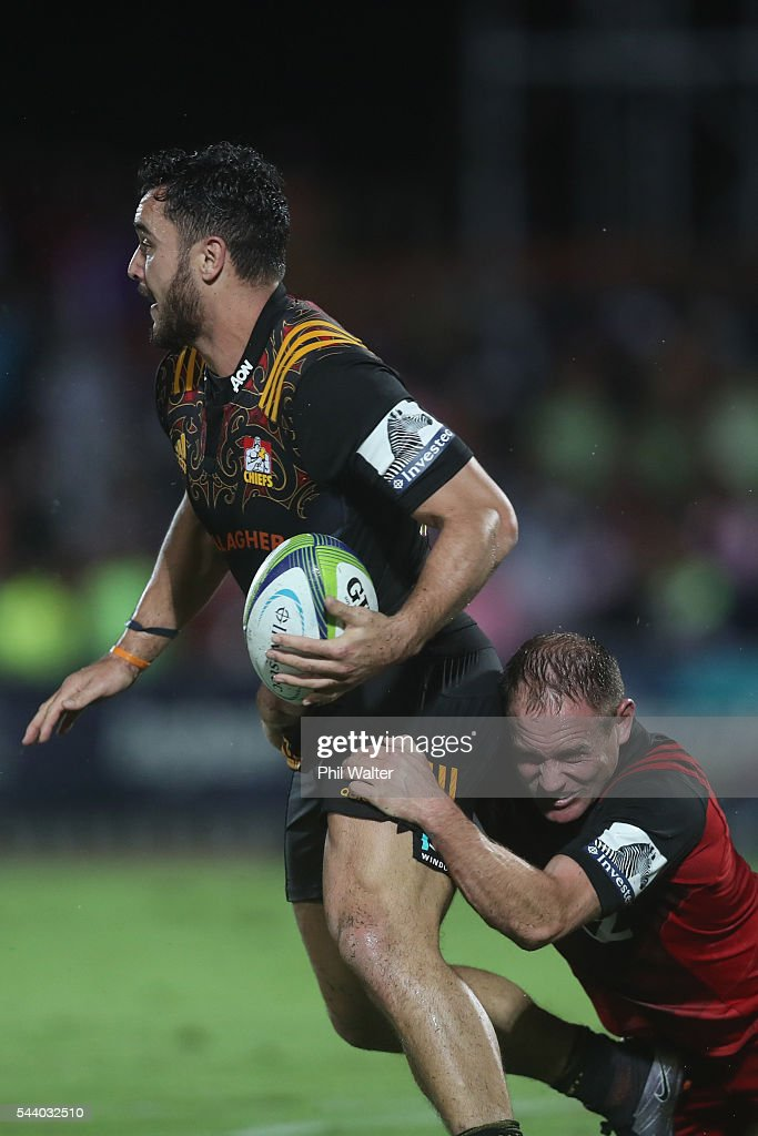 James Lowe of the Chiefs is tackled by Andy Ellis during the round 15 Super Rugby match between the Chiefs and the Crusaders at ANZ Stadium on July 1, 2016 in Suva, Fiji.