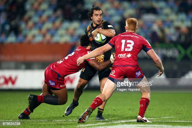 James Lowe of the Chiefs is tackled by Samu Kerevi and Campbell Magnay of the Reds during the round 11 Super Rugby match between the Chiefs and the...
