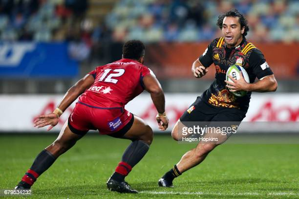 James Lowe of the Chiefs looks to beat the challenge of Samu Kerevi of the Reds during the round 11 Super Rugby match between the Chiefs and the Reds...