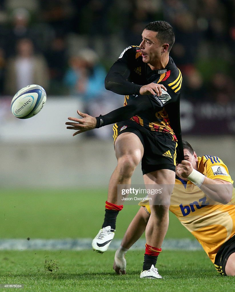 James Lowe of the Chiefs offloads in the tackle of Jeffery Toomaga-Allen of the Hurricanes during the round 18 Super Rugby match between the Chiefs and the Hurricanes at Waikato Stadium on July 4, 2014 in Hamilton, New Zealand.