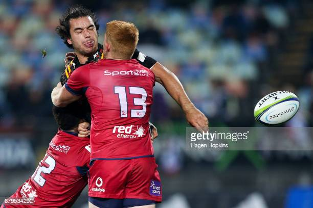 James Lowe of the Chiefs offloads in the tackle of Samu Kerevi and Campbell Magnay of the Reds during the round 11 Super Rugby match between the...