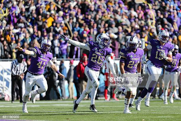 James Madison Dukes linebacker Justin Wellons cornerback Curtis Oliver and linebacker Brett Siegel run towards the sidelines in celebration during...