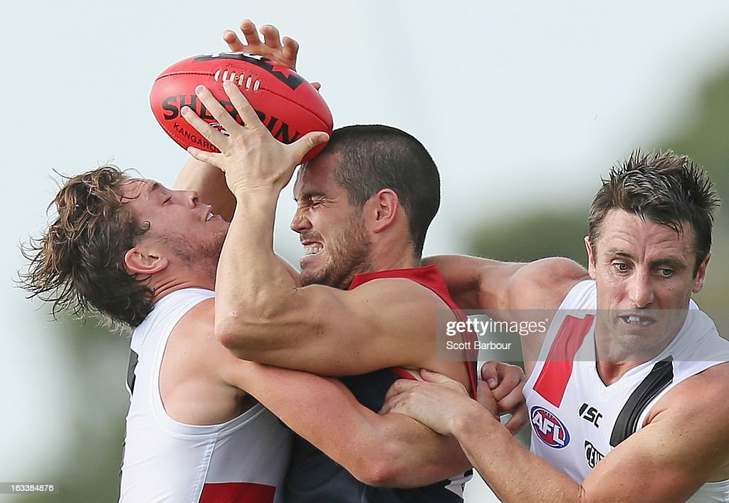 James Magner of the Demons is tackled by Jack Steven and <a gi-track='captionPersonalityLinkClicked' href=/galleries/search?phrase=Stephen+Milne&family=editorial&specificpeople=171906 ng-click='$event.stopPropagation()'>Stephen Milne</a> of the Saints during the round three NAB Cup AFL match between the Melbourne Demons and the St Kilda Saints at Casey Fields on March 9, 2013 in Melbourne, Australia.