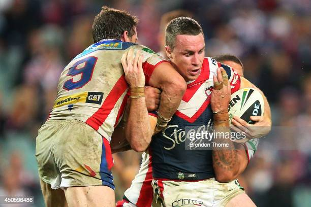James Maloney of the Roosters is tackled by the Knights defence during the round 14 NRL match between the Sydney Roosters and the Newcastle Knights...