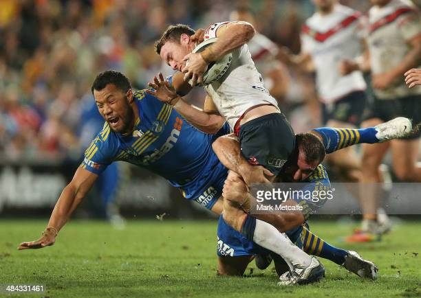 James Maloney of the Roosters is tackled by Tim Mannah and Joseph Paulo of the Eels during the round 6 NRL match between the Parramatta Eels and the...