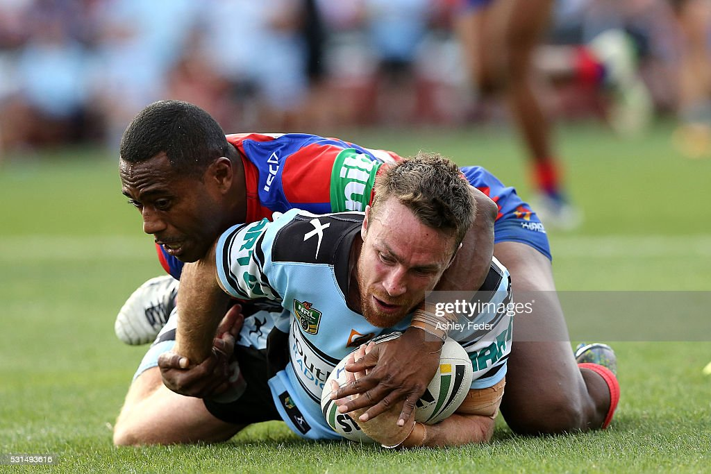 James Maloney of the Sharks is tackled by Akuila Uate of the Knights during the round 10 NRL match between the Newcastle Knights and the Cronulla Sharks at Hunter Stadium on May 15, 2016 in Newcastle, Australia.