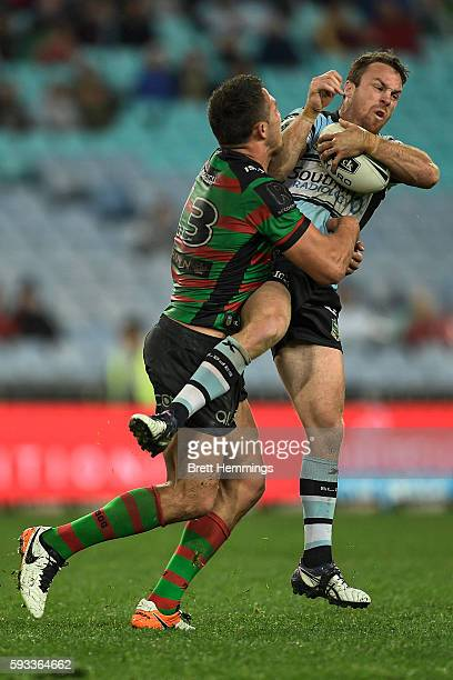 James Maloney of the Sharks is tackled by Samuel Burgess of the Rabbitohs during the round 24 NRL match between the South Sydney Rabbitohs and the...