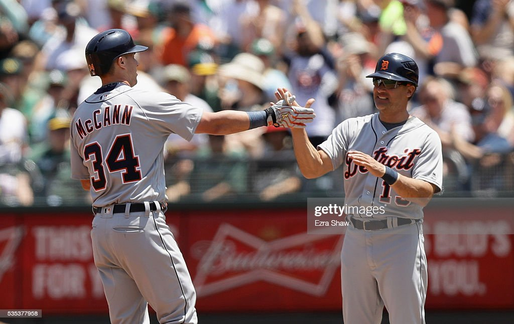 James McCann #34 of the Detroit Tigers is congratulated by first base coach first base coach <a gi-track='captionPersonalityLinkClicked' href=/galleries/search?phrase=Omar+Vizquel&family=editorial&specificpeople=201489 ng-click='$event.stopPropagation()'>Omar Vizquel</a> #13 after he hit a single that scored Nick Castellanos #9 in the second inning of their game against the Oakland Athletics at the Coliseum on May 29, 2016 in Oakland, California.