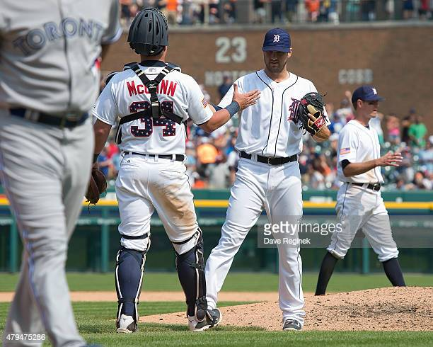 James McCann of the Detroit Tigers slaps hands with relief pitcher Drew VerHagen after defeating the Toronto Blue Jays 83 during a MLB game at...