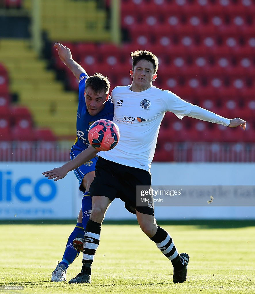 James McCarten of Warrington is challenged by John Oster of Gateshead during the FA Cup Second Round tie between Gateshead FC v and Warrington Town at the Gateshead International Stadium on December 7, 2014 in Gateshead, England.