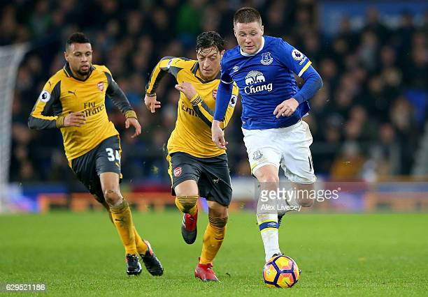 James McCarthy of Everton is pursued by Francis Coquelin and Mesut Ozil of Arsenal during the Premier League match between Everton and Arsenal at...