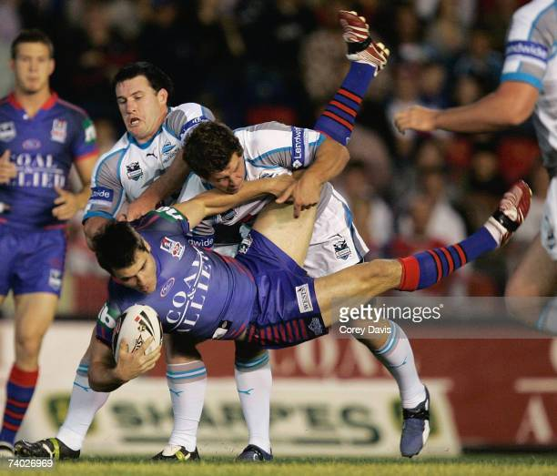 James McManus of the Knights is tackled by Sharks defence during the round seven NRL match between the Newcastle Knights and the Cronulla Sharks at...